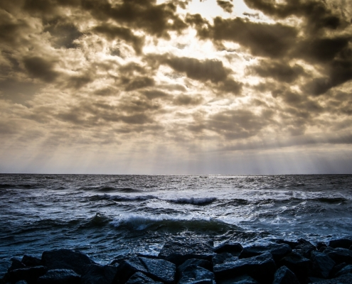 Waves at the sea and sunbeams shining through the clouds